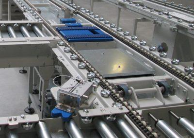 Kettenförderer mit Modulbandausschleuser und Rollenbahneckumsetzer